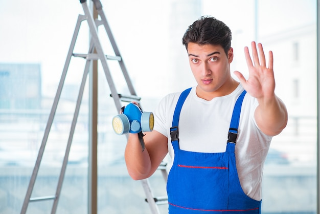 Junger arbeitnehmer mit schützender gesichtsgasmaske