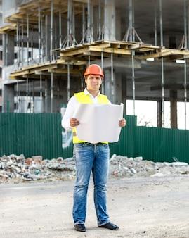 Junger architekt bei der arbeit beim lesen von bauplänen auf der baustelle