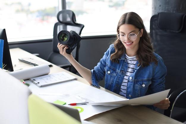 Junger architekt, der digitalkamera hält und auf blaupause schaut, während er im kreativbüro arbeitet.