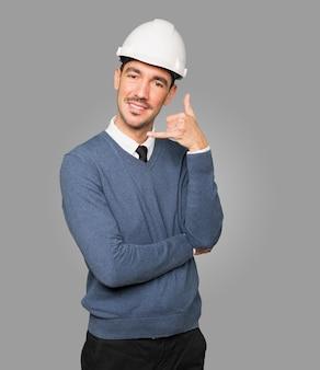 Junger architekt, der eine geste des rufens mit seiner hand macht