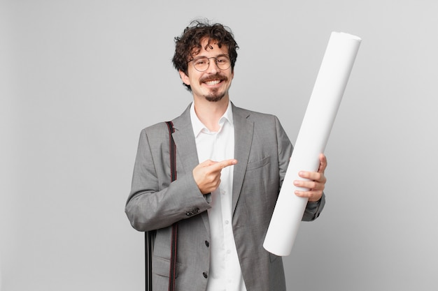 Junger architekt, der fröhlich lächelt, sich glücklich fühlt und zur seite zeigt