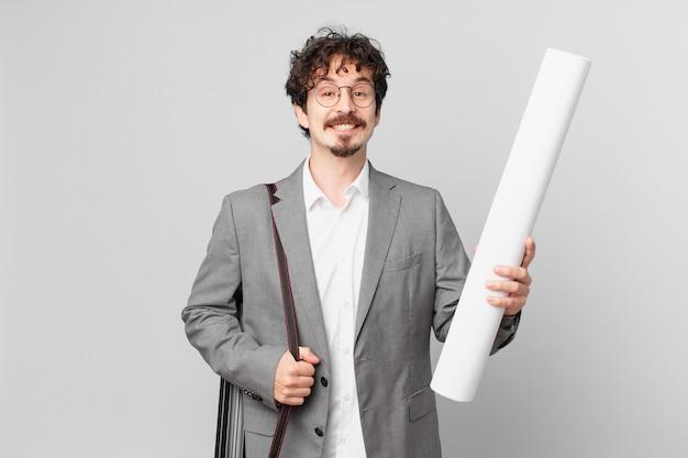 Junger architekt, der glücklich mit einer hand auf der hüfte und selbstbewusst lächelt