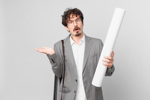 Junger architekt, der überrascht und schockiert aussieht, mit heruntergefallenem kiefer, der ein objekt hält