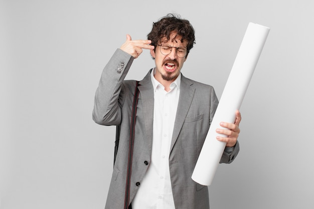 Junger architekt, der unglücklich und gestresst aussieht, selbstmordgeste, die waffenzeichen macht