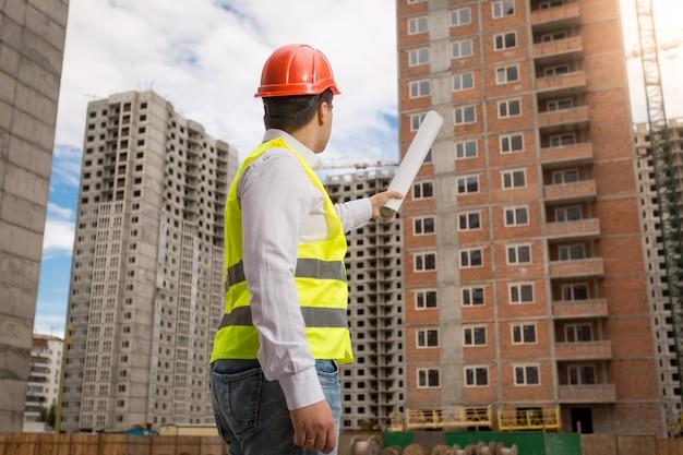 Junger architekt in bauarbeiterhelm und warnweste, der gebäude mit gerollten blaupausen zeigt