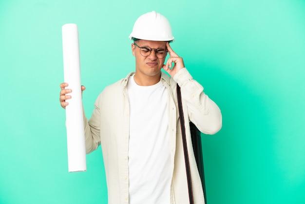 Junger architekt mann, der blaupausen über isoliertem hintergrund mit kopfschmerzen hält