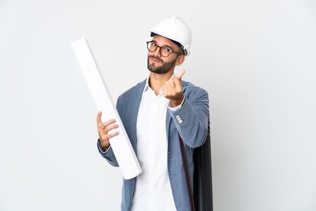 Junger architekt mann mit helm und blaupausen isoliert auf weißem hintergrund macht geldgeste