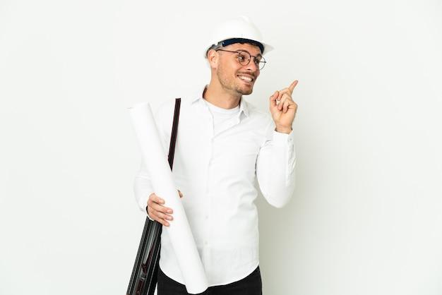 Junger architekt mann mit helm und hält blaupausen isoliert auf weißem hintergrund mit der absicht, die lösung zu realisieren, während er einen finger hochhebt