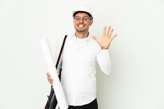 Junger architekt mann mit helm und hält blaupausen isoliert auf weißem hintergrund und zählt fünf mit den fingern