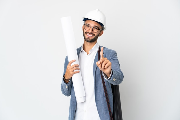 Junger architekt mann mit helm und hält blaupausen isoliert auf weißem hintergrund zeigt und hebt einen finger