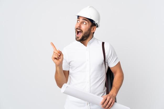 Junger architekt mann mit helm und hält blaupausen isoliert auf weißer wand in der absicht, die lösung zu realisieren, während ein finger angehoben wird