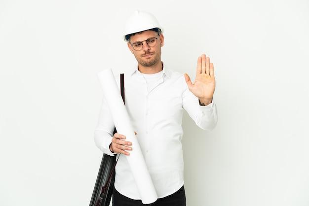 Junger architekt mann mit helm und hält blaupausen lokalisiert auf weiß, das stoppgeste macht und enttäuscht