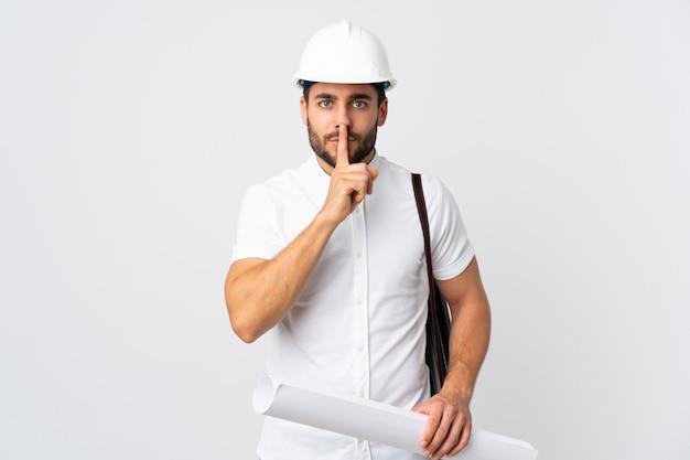 Junger architekt mann mit helm und hält blaupausen lokalisiert auf weißer wand, die ein zeichen der stille geste zeigt finger in den mund setzen