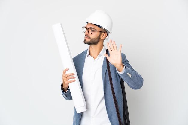 Junger architekt mann mit helm und hält blaupausen lokalisiert auf weißer wand, die stoppgeste und enttäuscht macht