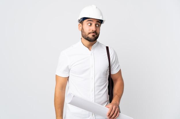 Junger architekt mann mit helm und hält blaupausen lokalisiert auf weißer wand, die zweifel gestikulierende seite macht