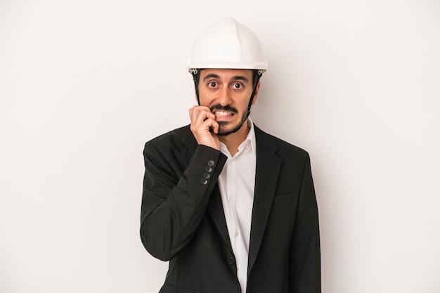 Junger architekt mann trägt einen bauhelm auf weißem hintergrund beißende fingernägel, nervös und sehr ängstlich.