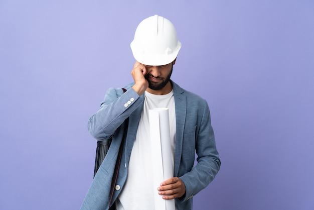 Junger architekt mit helm, der am telefon spricht und blaupausen hält