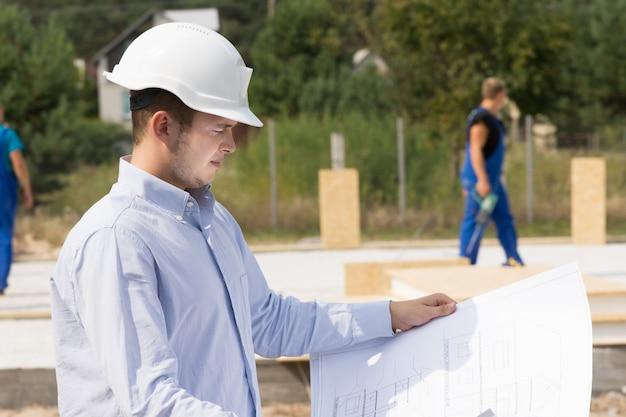 Junger architekt oder ingenieur, der die spezifikationen auf einem plan oder einer blaupause überprüft, während er mit blick auf die baustelle steht