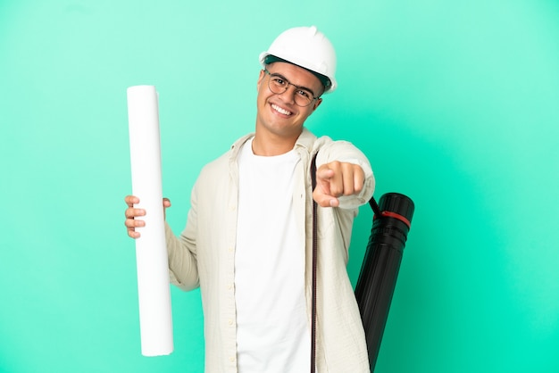 Junger architektenmann, der blaupausen über isolierter wand hält, die mit glücklichem ausdruck nach vorne zeigt