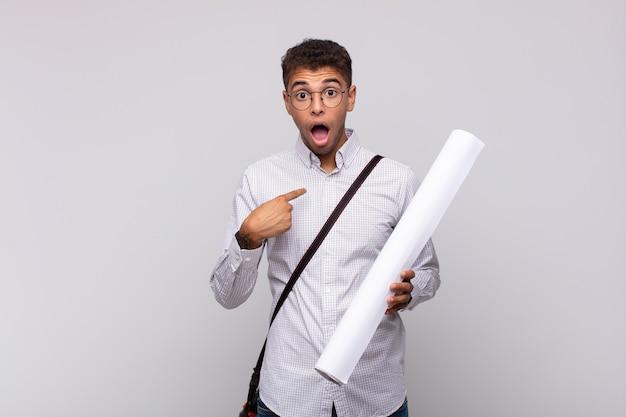 Junger architektenmann, der schockiert und überrascht mit weit geöffnetem mund aussieht und auf sich selbst zeigt