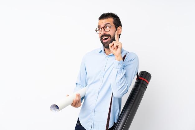Junger architektenmann mit bart über der lokalisierten weißen wand, die beabsichtigt, die lösung beim anheben eines fingers zu verwirklichen