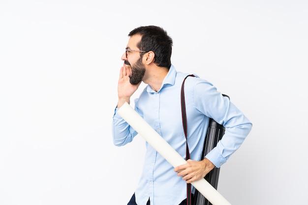 Junger architektenmann mit bart über der lokalisierten weißen wand, die mit dem breiten mund schreit, öffnen sich zur seite