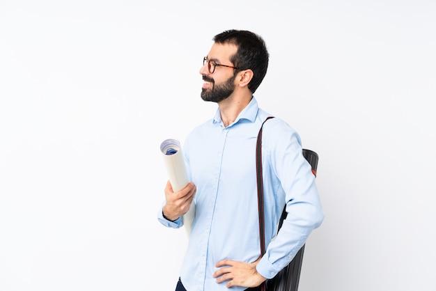 Junger architektenmann mit bart über der lokalisierten weißen wand, die zur seite schaut