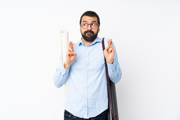 Junger architektenmann mit bart über lokalisiertem weiß mit den fingern, die das beste kreuzen und wünschen
