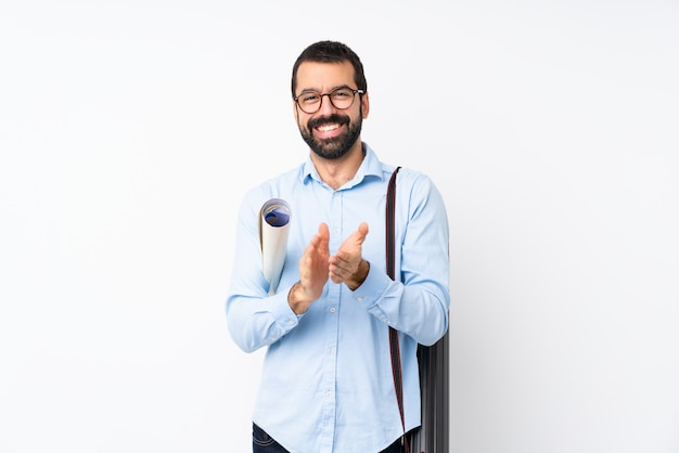 Junger architektenmann mit bart über lokalisierter weißer wand, die nach darstellung in einer konferenz applaudiert