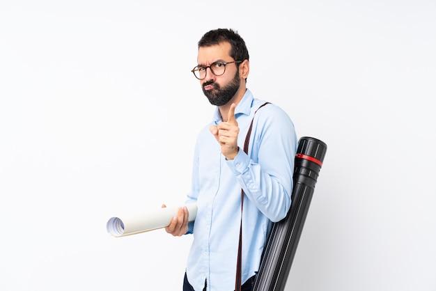 Junger architektenmann mit bart über lokalisierter weißer wand frustriert und auf die front zeigend