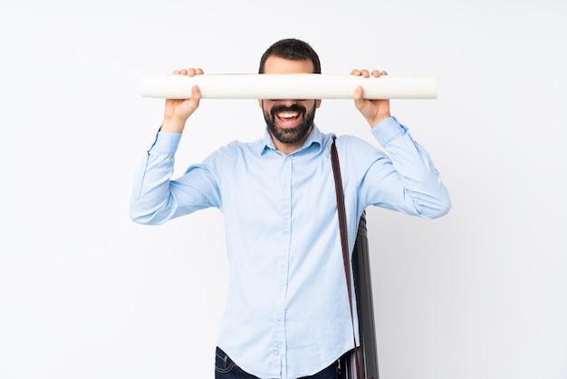 Junger architektenmann mit bart über lokalisierter weißer wandverkleidung mustert durch hände