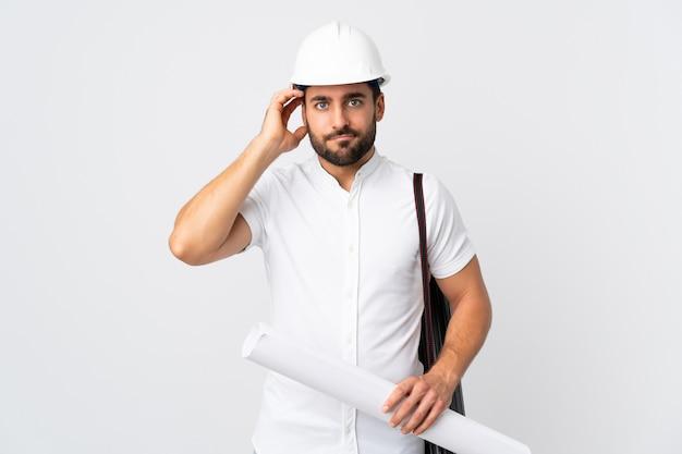 Junger architektenmann mit helm und blaupausen auf weißer wand mit einem ausdruck der frustration und des nichtverständnisses