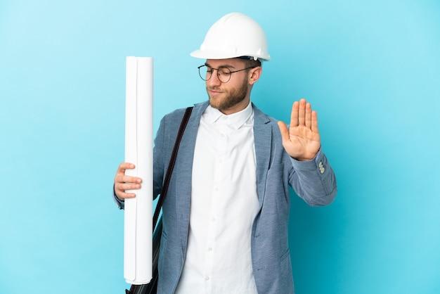 Junger architektenmann mit helm und blaupausen über isolierter wand, die stoppgeste und enttäuscht macht