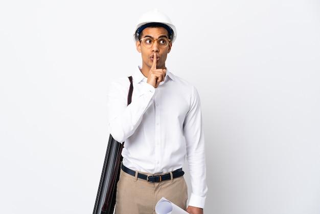 Junger architektenmann mit helm und blaupausen über isolierter weißer wand, die ein zeichen der schweigegeste zeigt, die finger in den mund setzt