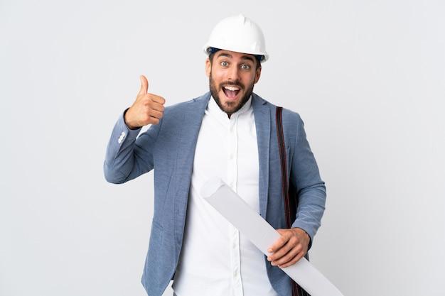 Junger architektenmann mit helm und hält blaupausen lokalisiert auf weißer wand, die eine daumen hoch geste geben
