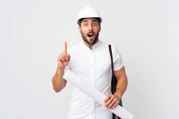 Junger architektenmann mit helm und hält blaupausen lokalisiert auf weißer wand, die eine idee denkt, die den finger nach oben zeigt
