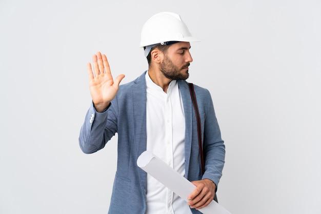 Junger architektenmann mit helm und hält blaupausen lokalisiert auf weißer wand, die stoppgeste und enttäuscht macht