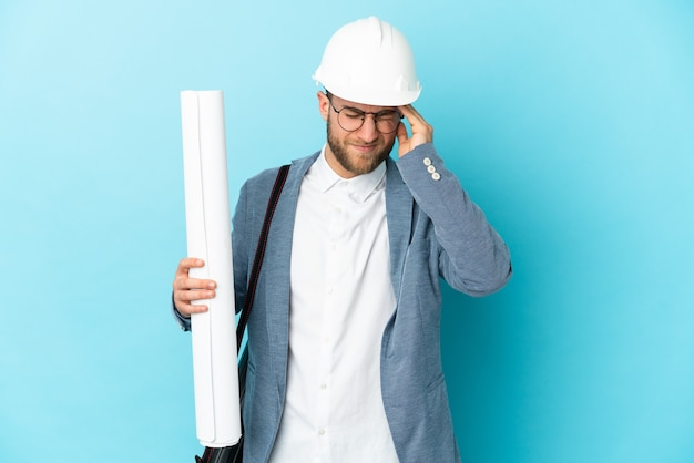 Junger architektenmann mit helm und hält blaupausen über lokalisiertem hintergrund mit kopfschmerzen