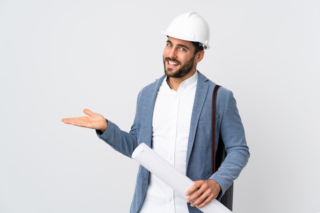 Junger architektenmann mit helm und halten der blaupausen lokalisiert auf weißer wand, die eine idee darstellt, während sie lächelnd in richtung schaut