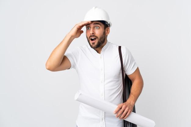 Junger architektenmann mit helm und halten von blaupausen lokalisiert auf weiß mit überraschungsausdruck beim betrachten der seite