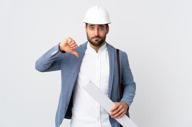 Junger architektenmann mit helm und halteplänen lokalisiert auf weiß, das daumen unten mit negativem ausdruck zeigt