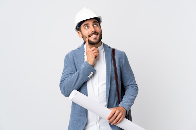 Junger architektenmann mit helm und halteplänen lokalisiert auf weiß, das eine idee beim nachschlagen denkt