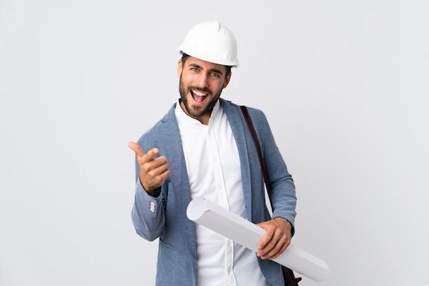 Junger architektenmann mit helm und halteplänen lokalisiert auf weiß, das nach vorne zeigt und lächelt