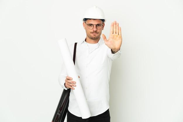 Junger architektenmann mit helm und halteplänen lokalisiert auf weißem hintergrund, der stoppgeste macht