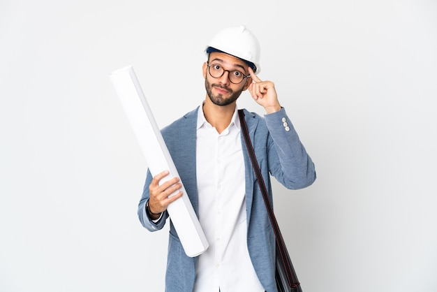 Junger architektenmann mit helm und halteplänen lokalisiert auf weißer wand, die eine idee denkt