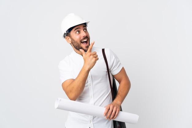Junger architektenmann mit helm und halteplänen lokalisiert auf weißer wand, die mit dem zeigefinger eine große idee zeigt
