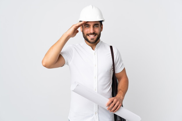 Junger architektenmann mit helm und halteplänen lokalisiert auf weißer wand, die mit hand mit glücklichem ausdruck salutiert