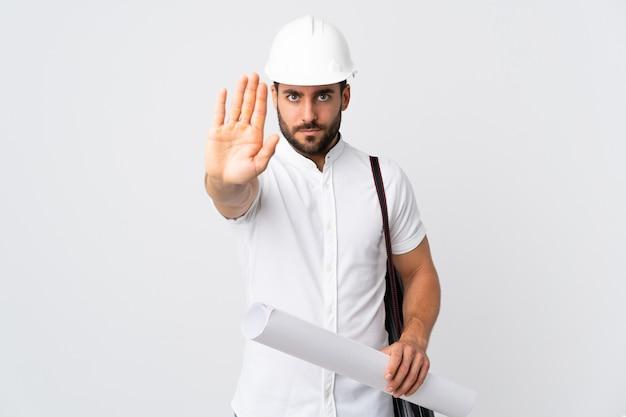 Junger architektenmann mit helm und halteplänen lokalisiert auf weißer wand, die stoppgeste macht