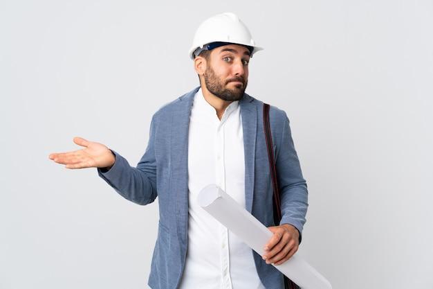 Junger architektenmann mit helm und halteplänen lokalisiert auf weißer wand, die zweifel gestikulieren