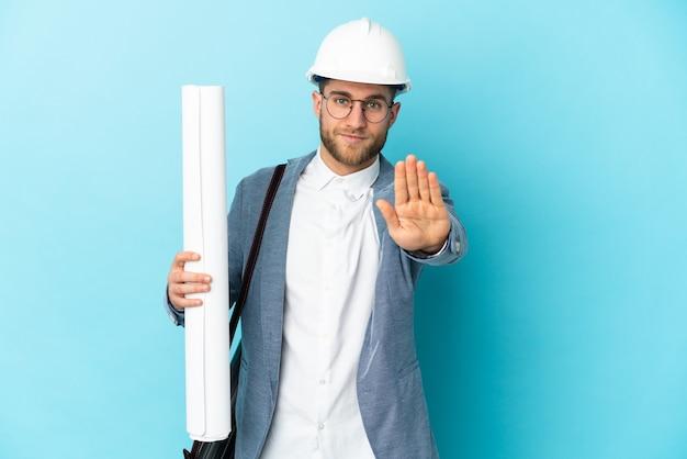 Junger architektenmann mit helm und halteplänen lokalisiert